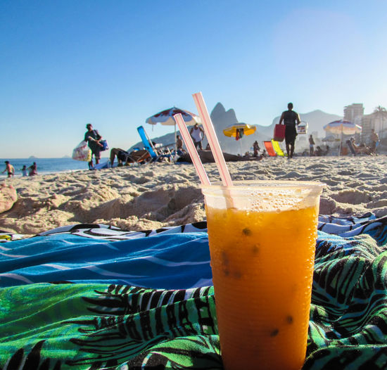 Close-Up Of Drink On Shore Against Clear Blue Sky At Beach