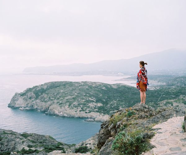 Woman standing on mountain by sea against sky