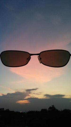 Silhouette of sunglasses against sky during sunset