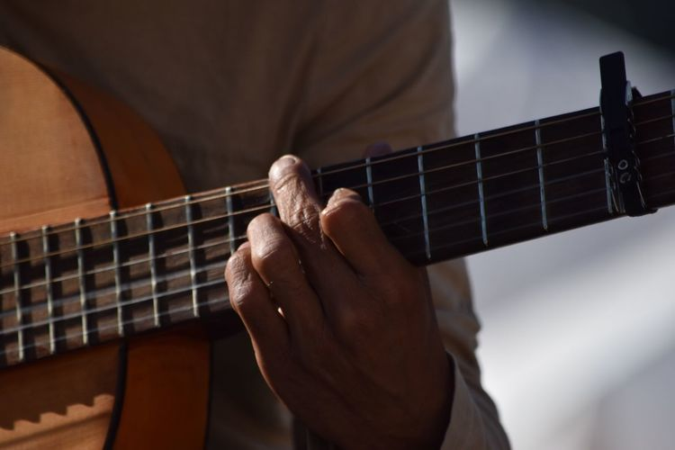 Close-up midsection of man playing guitar