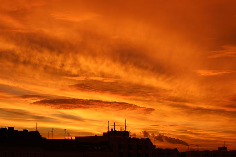 Silhouette buildings against sky during sunset