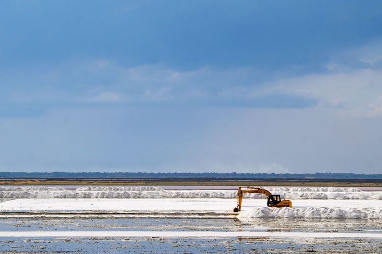 Construction machinery on frozen land against sky