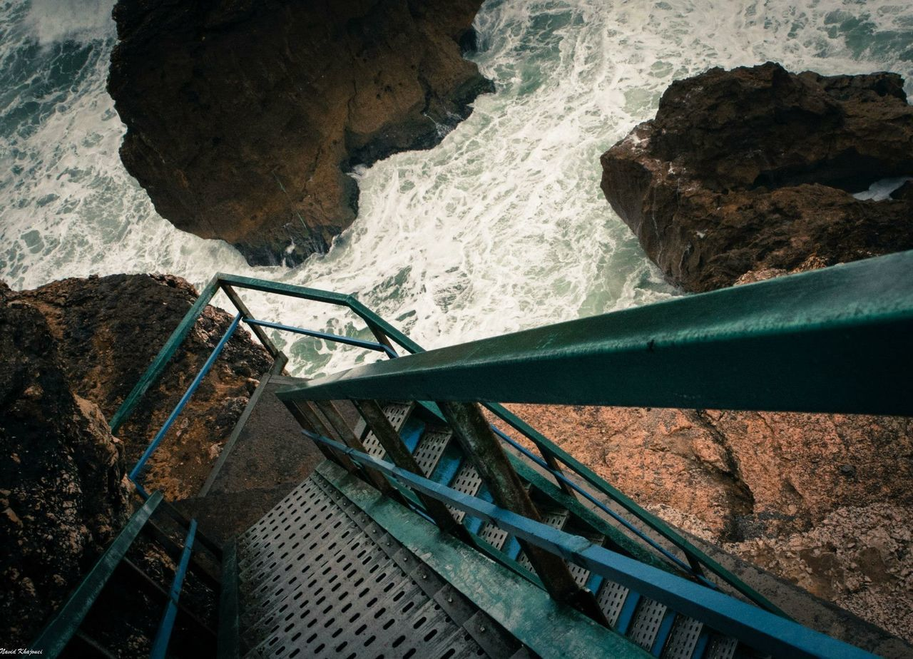 Metallic stairs leading towards sea