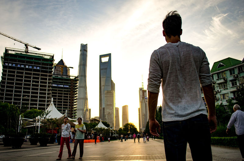 Rear view of man standing against sky in city