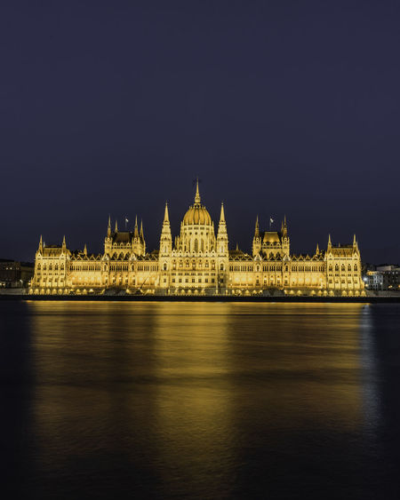 Illuminated hungarian parliament building by river against sky at night
