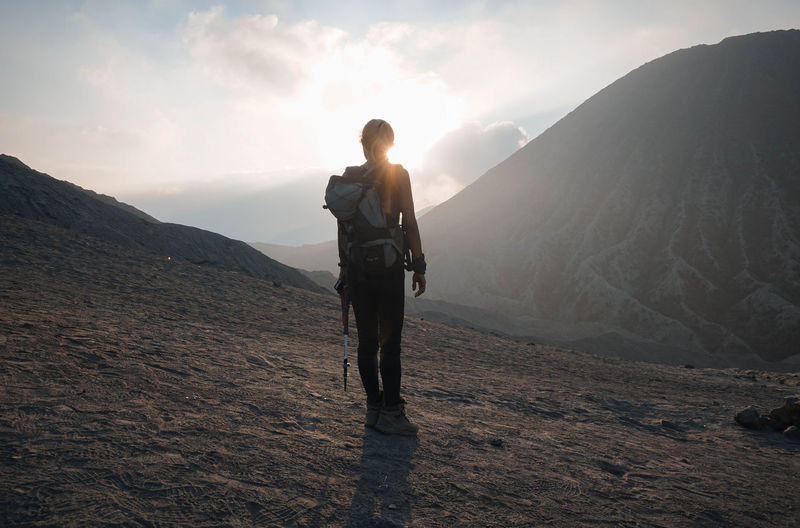 Rear view of backpack woman standing on land by mountains