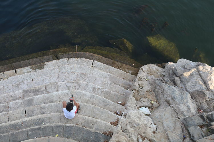 A Bird's Eye View Casual Clothing Circle Day Fishing Full Length High Angle View Leisure Activity Lifestyles Men Nature Nile River Non-urban Scene Outdoors River Steps Stone Material Swimming Tourism People And Places Tranquility Vacations Water Hidden Gems  Fatherhood Moments
