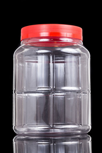 Plastic jar bottle container with red cover lid against dark background Black Background Bottle Close-up Container Cut Out Glass - Material Healthcare And Medicine Indoors  Jar No People Plastic Science Single Object Still Life Studio Shot Transparent