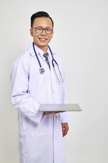 Portrait Of Smiling Doctor Holding Laptop Against White Background