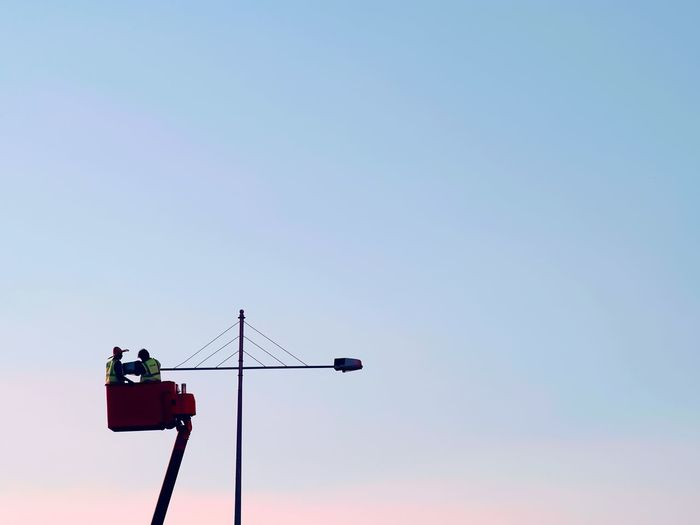 Low angle view of men in cherry picker repairing light against clear sky