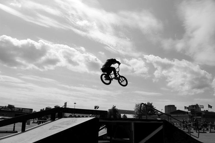 Low angle view of man performing stunt with bicycle in park against sky