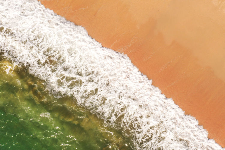 Aerial image of white surf splashing on a sandy beach with emerald green ocean
