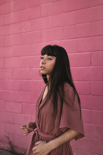 Woman looking away while standing against pink wall
