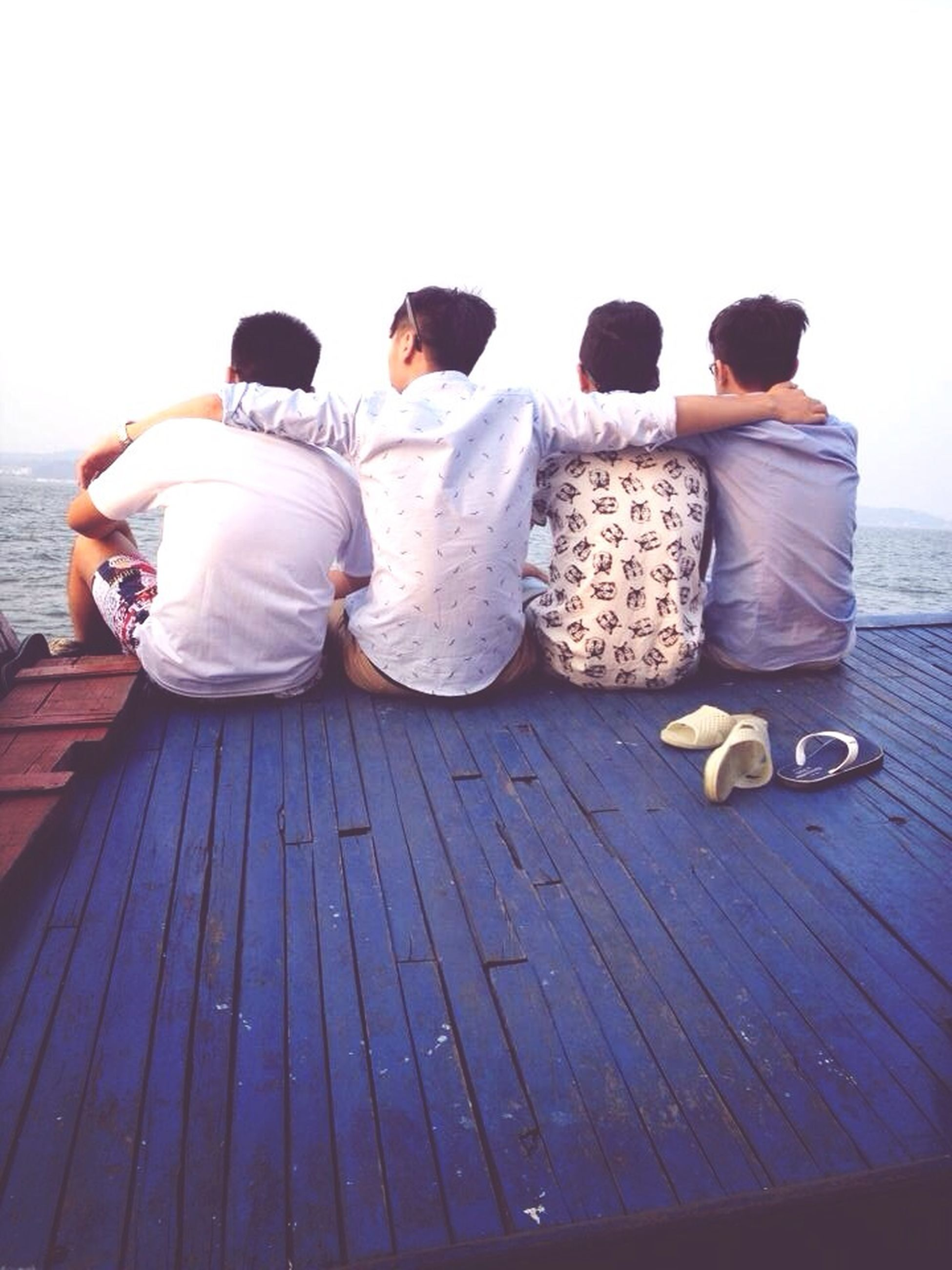 rear view, lifestyles, leisure activity, togetherness, men, full length, sitting, clear sky, casual clothing, relaxation, person, bonding, water, copy space, standing, sea