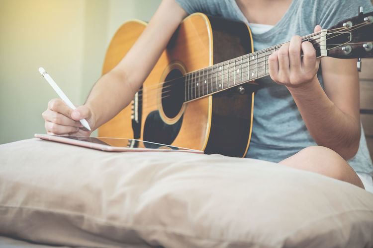 Midsection Of Woman Playing Guitar While Using Digital Tablet On Bed
