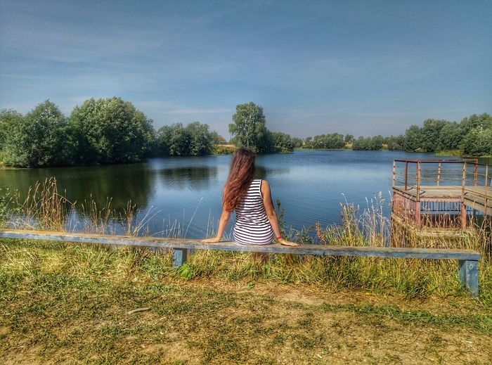Woman by lake against sky