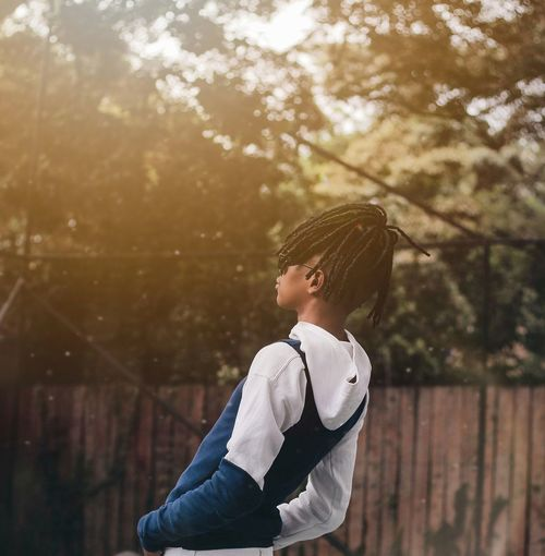 Side view of boy standing against trees