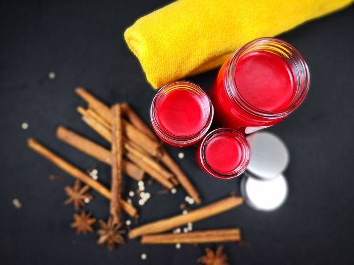 Directly above shot of red lip balm with spice on table