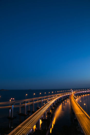 Illuminated light trails on bridge at night