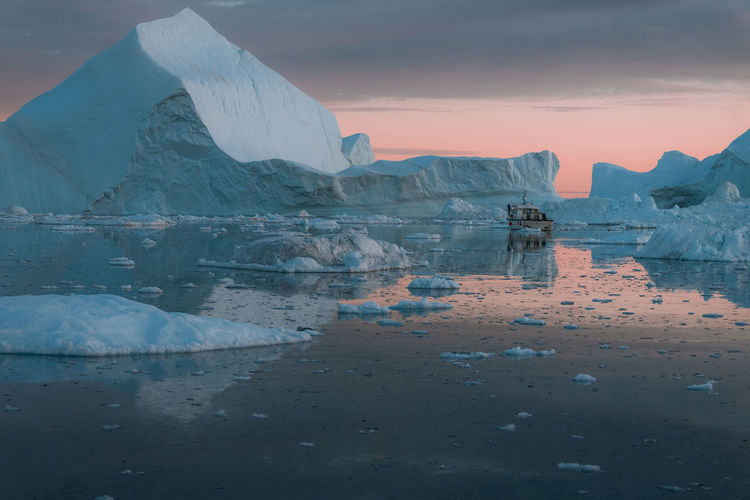 """Icebergs in a sunset depicting the color pantone of the year """"living coral"""" Water Ice Glacier Cold Temperature Sky Scenics - Nature Beauty In Nature Tranquility Reflection Tranquil Scene Frozen Sea Winter Iceberg Nature Waterfront Sunset Environment Landscape Floating On Water Melting Boat"""