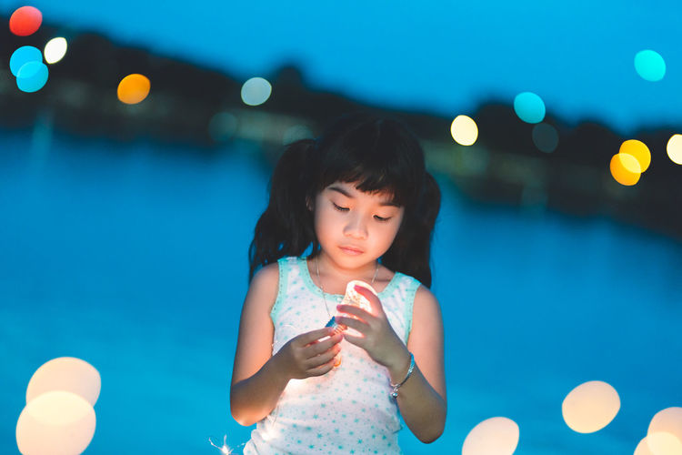 Girl looking at illuminated light bulb while standing against river at night