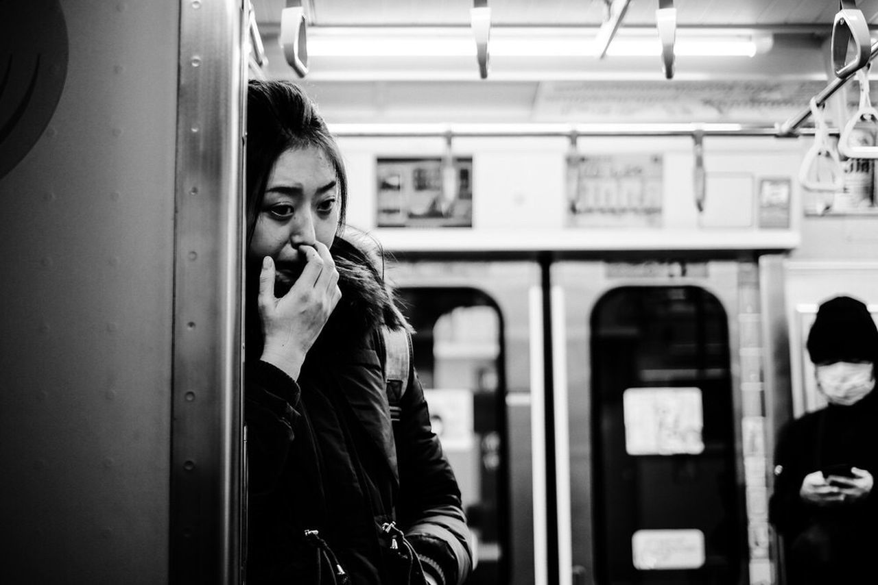 real people, one person, public transportation, train, lifestyles, young adult, young women, train - vehicle, portrait, mode of transportation, leisure activity, rail transportation, front view, transportation, women, casual clothing, warm clothing, standing, clothing, scarf, subway train