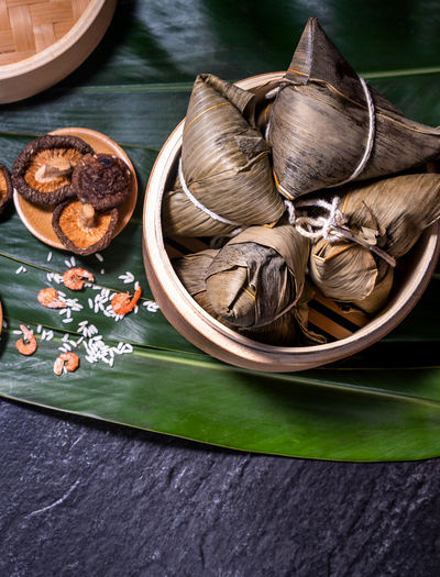 Zongzi Hand Girl Rice Dumpling  Duanwu Festival Dragon Boat Steamer Steam Dark Background Taiwan Chinese Food Gourmet Cuisine Culture Black Slate Meal Bamboo Leaf Vapor Fillings Green Fresh Traditional Lifestyle Tamale Holiday Table Tradition Objects Layout Closeup Flatlay Copyspace Topview Mushroom Peanut Glutinous Sticky Dried Shrimp Ingredient Summer ASIA Wrapped