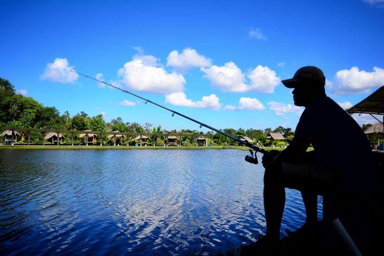Man fishing in water against blue sky