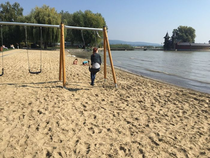 Rear View Of Female Sitting On Swing While Children Playing At Beach