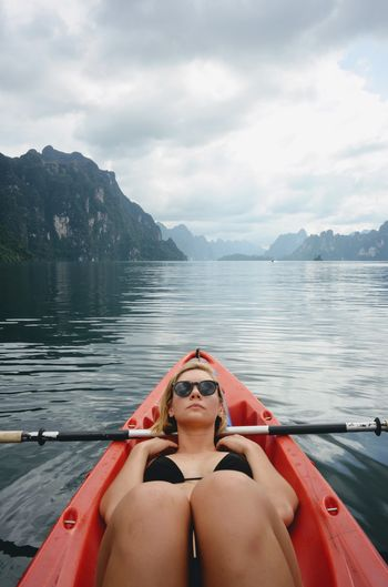 Young Woman Lying In Boat On Lake Against Sky