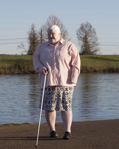 Portrait of woman holding stick while standing by lake against sky