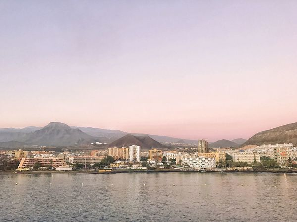 Tenerife view from the ferry. Sunset Dawn Architecture Water Sky Built Structure Building Exterior City Building Mountain Sea Clear Sky Mountain Range Scenics - Nature Waterfront Beach Cityscape Residential District