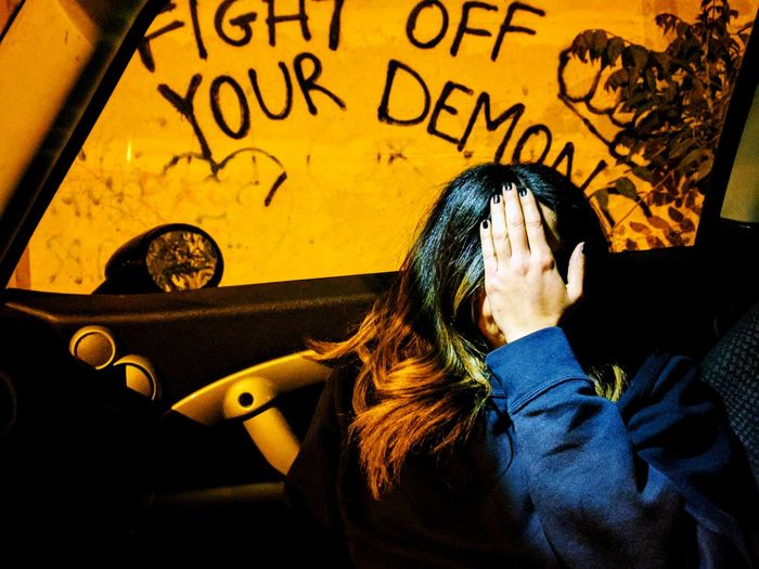 Woman Covering Face While Sitting In Car Against Graffiti On Wall