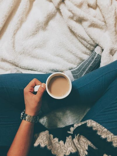 Low section of woman having tea on bed at home