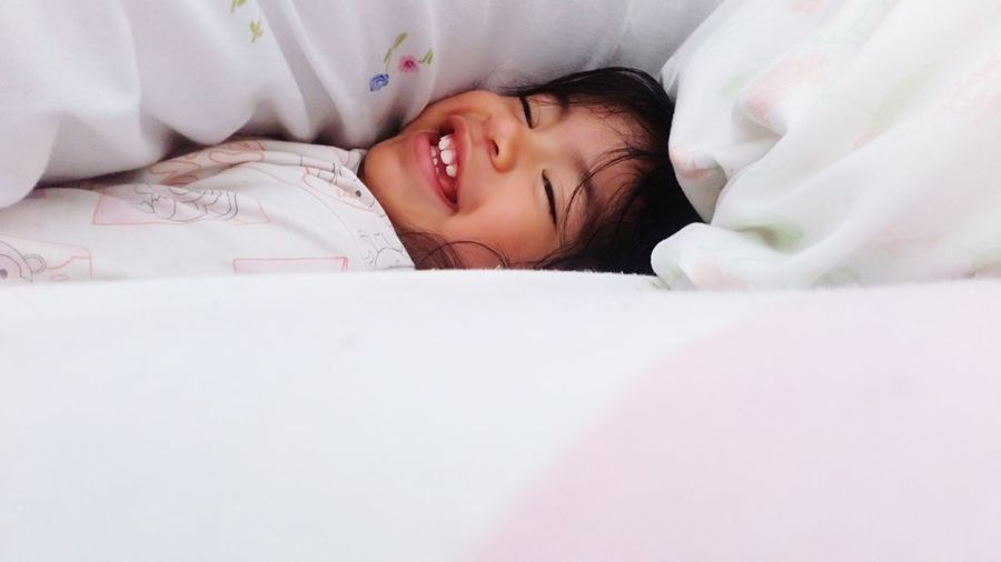 Girl smiling while lying on bed at home