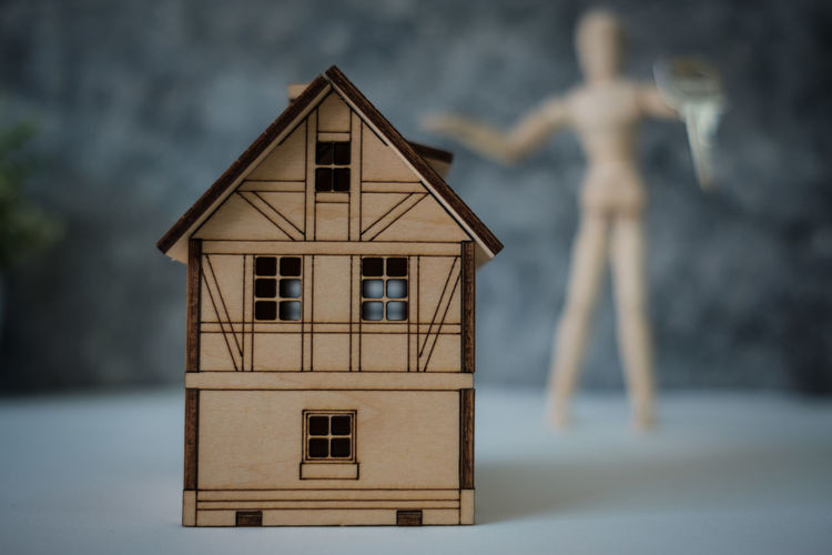 Close-Up Of Model Home With Figurine In Background