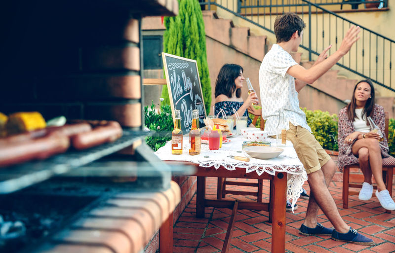 Close-Up Of Food On Barbecue Grill With Friends Talking In Background