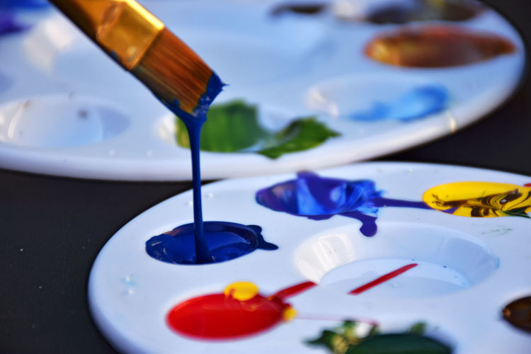 Close-up of paintbrushes over palette on table