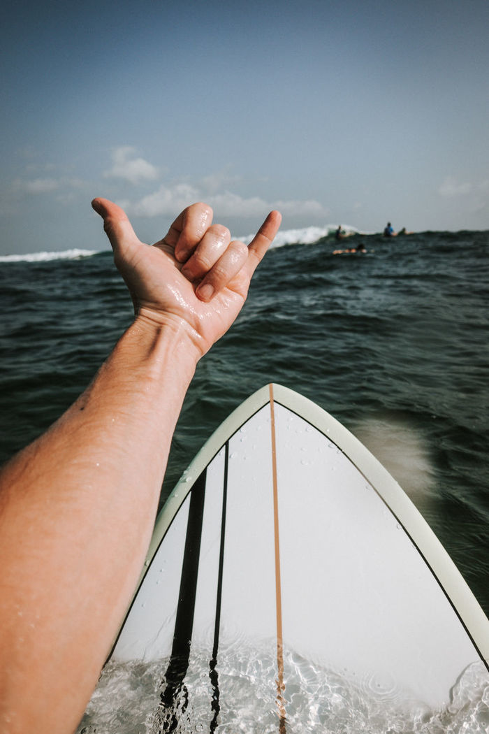 Cropped image of hand gesturing against in sea against sky