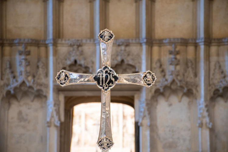 Crucifix with church interior in background No People Metal Focus On Foreground Religion Silver Colored Crucifix Cross Selective Focus Ornate Christian