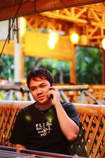 Portrait of young man using mobile phone at restaurant