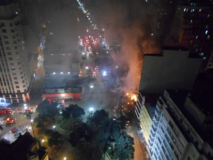 Inner City Calamity in downtown São Paulo at Largo do Paissandú; 3 am May 1, 2018. The abandoned former Federal Police steel and glass skyscraper, which had been invaded by street people, imploded this early morning and the neighboring building has caught on fire as well. 3 Am City City Life Destruction Largo Do Paissandu May 1, 2018 Night Photography Susan A. Case Sabir Unretouched Photography Building Fire Building Implosion Burning Building Controlled Chaos Dangerous Situation Downtown São Paulo High Angle View Illuminated Implosion Night Responsiveness Smoke - Physical Structure Unexpected Event Urban Photography Urban Strife
