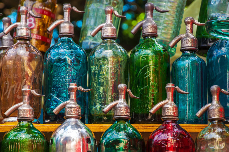 Colorful antique soda bottles in a market in Buenos Aires Antique Argentina Blue Bottles Buenos Aires Colorful Fair Green Market Red Retro Sale San Telmo San Telmo Fair Seltzer Seltzer Bottle Seltzer Water Siphon Soda South America Stall Vintage