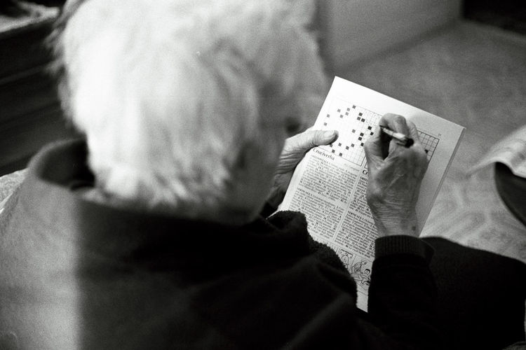 High Angle View Of Senior Woman Solving Crossword Puzzle