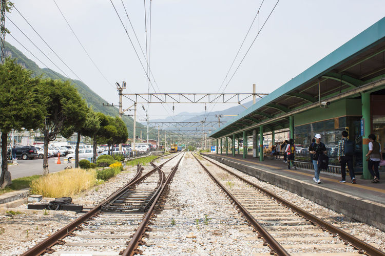 Railroad Station Track Rail Transportation Railroad Track Transportation Cable Day Railroad Station Platform Train Outdoors Group Of People Travel Direction Diminishing Perspective Power Line