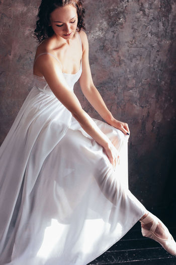 Ballet dancer ballerina in beautiful thin flying white dress is posing in dark loft studio Women One Person Beautiful Woman Young Adult Beauty Real People Young Women Adult Event Fashion Dress Clothing Wedding Newlywed Bride Lifestyles Wedding Dress Elégance Evening Gown Hairstyle Contemplation