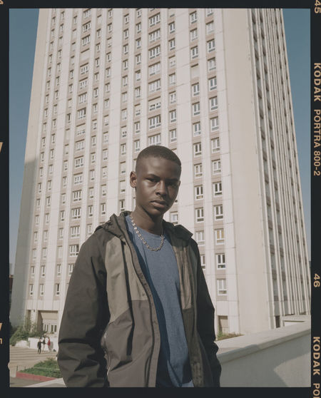 Low angle view of young man standing against buildings in city
