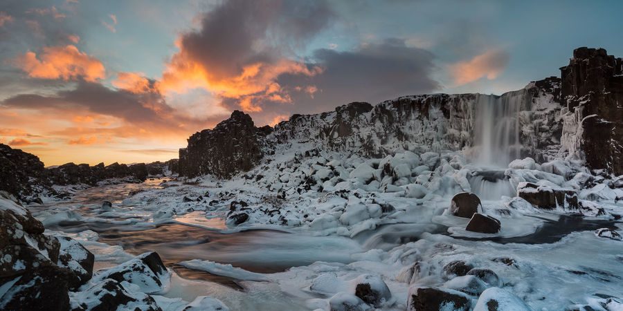 Fire and ice sunset by freezing waterfall, Iceland Oxarafoss Waterfall Iceland Travel Beauty In Nature Cloud - Sky Cold Temperature Environment Frozen Idyllic Nature No People Non-urban Scene Orange Color Power In Nature Scenics - Nature Sky Snow Sunset Tranquil Scene Tranquility Water Winter