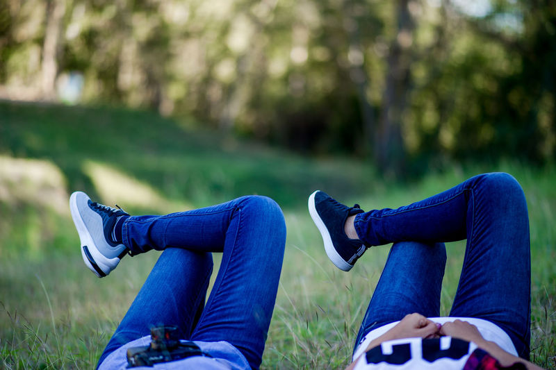 Low section of friends lying on grass