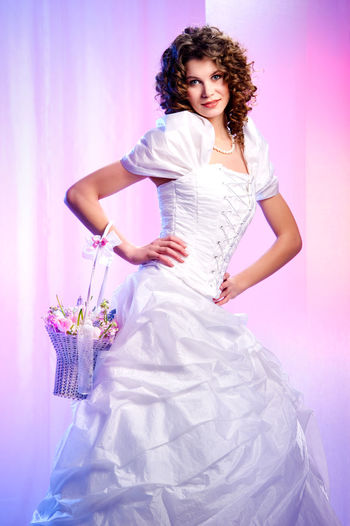Portrait Of Beautiful Bride With Bouquet Standing Against Colored Background